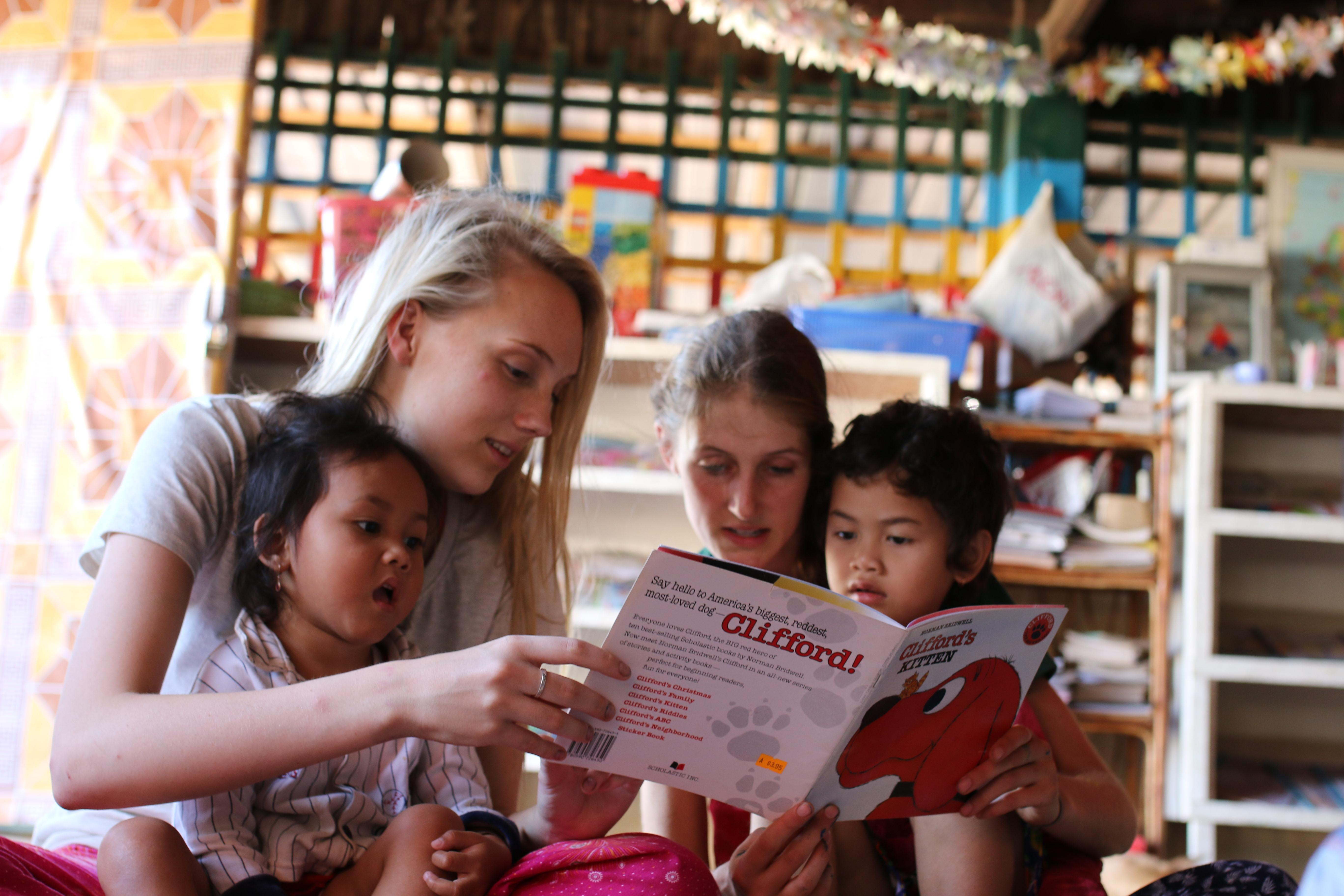 Cambodian children read aloud with two Childcare volunteers working abroad at a kindergarten,